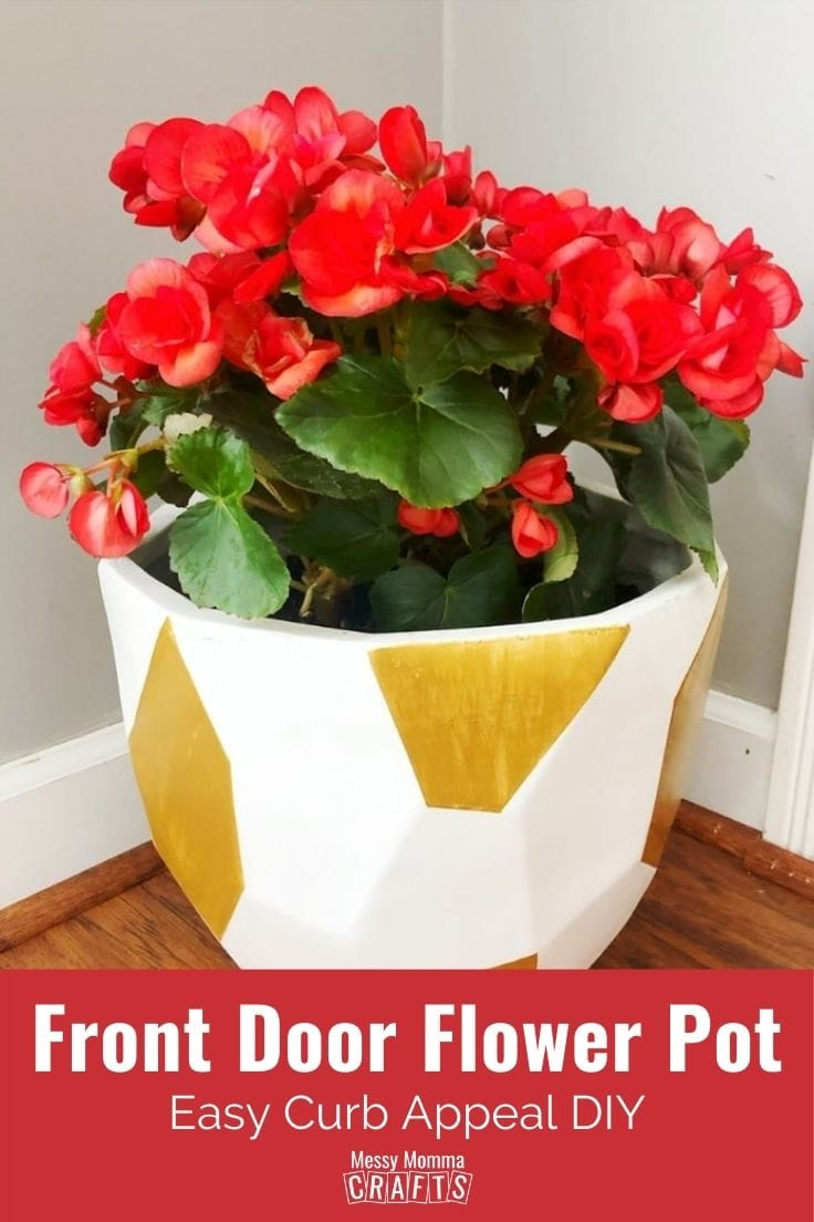 White front door flower pot painted with gold accents and filled with red flowers.