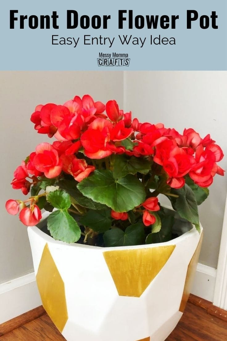White and gold front door flower pot with red flowers.