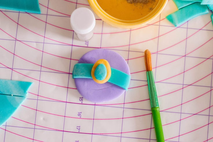 Brushing on some edible glitter to make these oh-so easy Princess Jasmine Cupcake Toppers