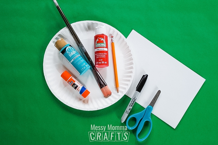 Paper plate, glue stick, paint, paintbrush, pencil, sharpie, and scissors.