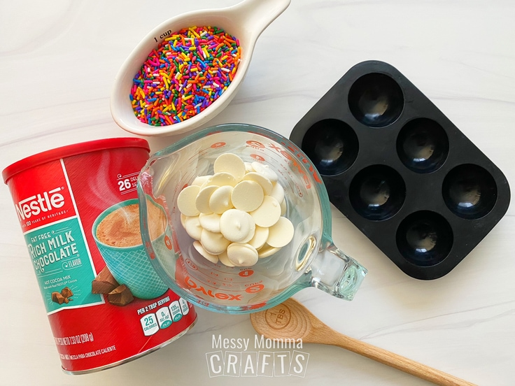 Nestle quick cocoa mix, a cup of white chocolate pieces, and a cup of rainbow sprinkles beside a hot cocoa bomb mold.