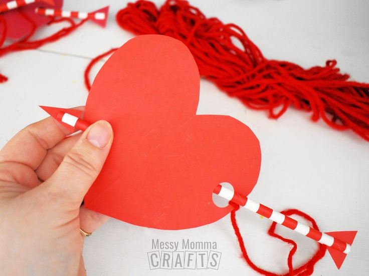 Red paper heart with a straw arrow through the middle.