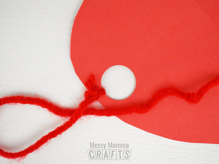 Red yarn tied to a hole in a paper heart.