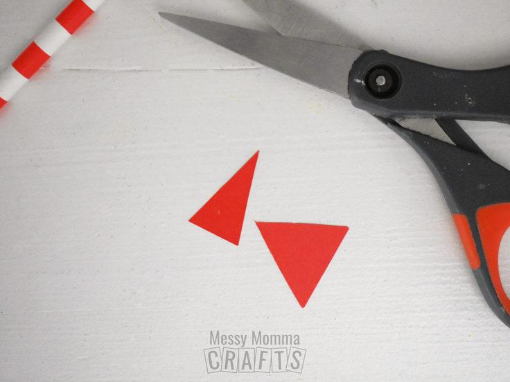 Scissors cutting red paper triangles.
