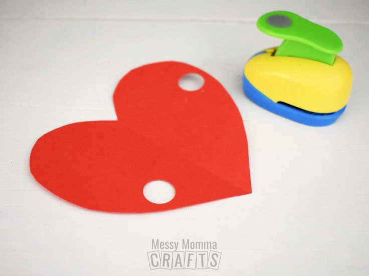 Paper heart with 2 holes punched in either side.