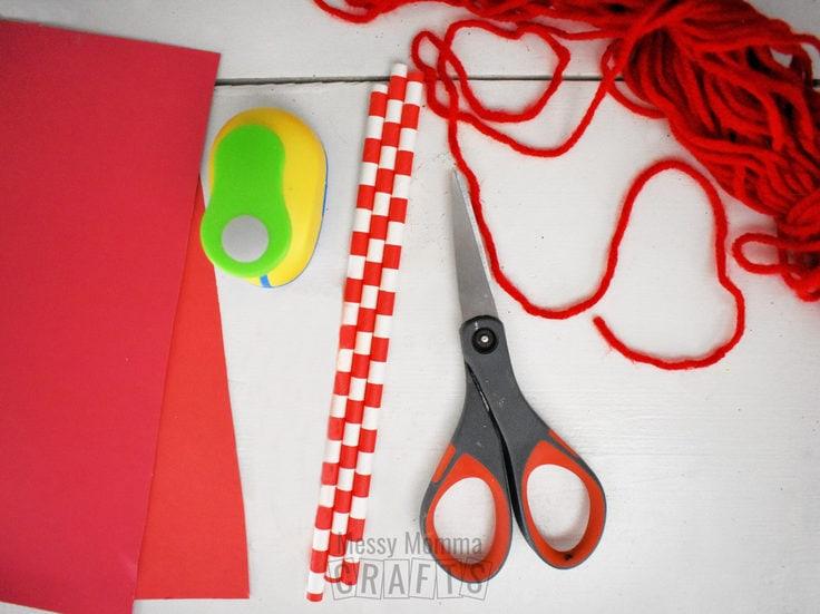 Craft paper, scissors, straws, and yarn.
