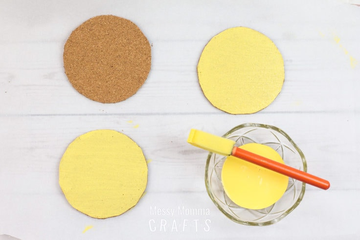 Circles of cork being painted yellow.