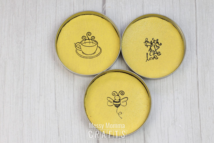 3 finished coasters with artwork inside mason jar lids.