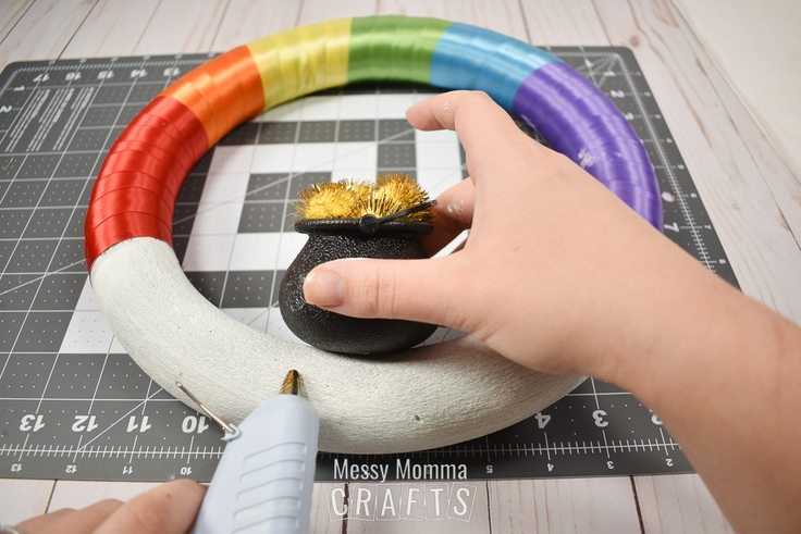 Adding a pot of gold to the rainbow wreath.