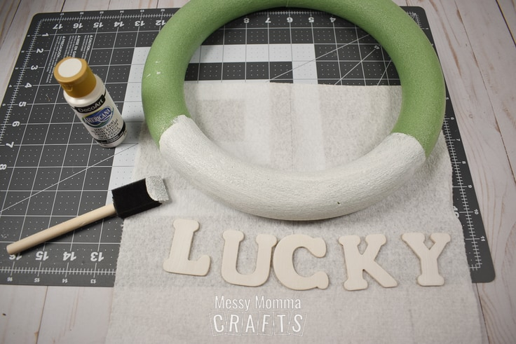 Painting a green Styrofoam wreath form white.