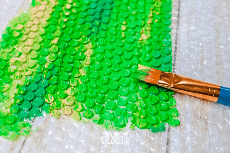 Green and yellow paint spread on bubble wrap.