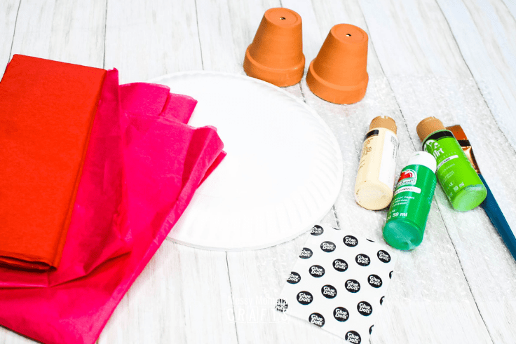 Red and pink tissue paper, paper plates, green and yellow paint, mini terra cotta pots, a paint brush, and Glue Dots.