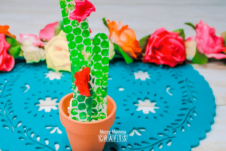 Terra cotta pot with a green paper cactus and pink blossoms.