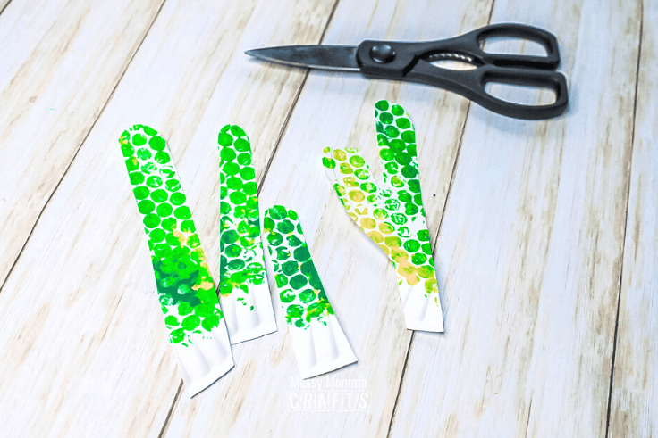 Printed paper plates cut into long cactus shapes.