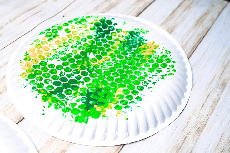 White paper plate stamped with green and yellow dots.