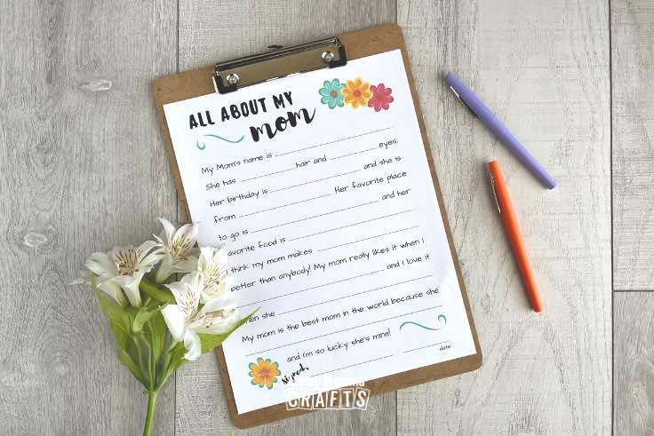 All About My Mom Printable interview worksheet in a frame with pens & flowers on a wood backdrop.