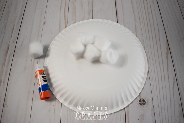 Gluing cotton balls to a white paper plate.