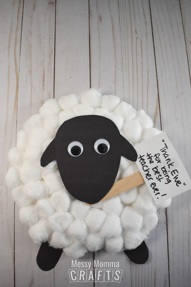 Kids' sheep craft made from cotton balls and black construction paper.