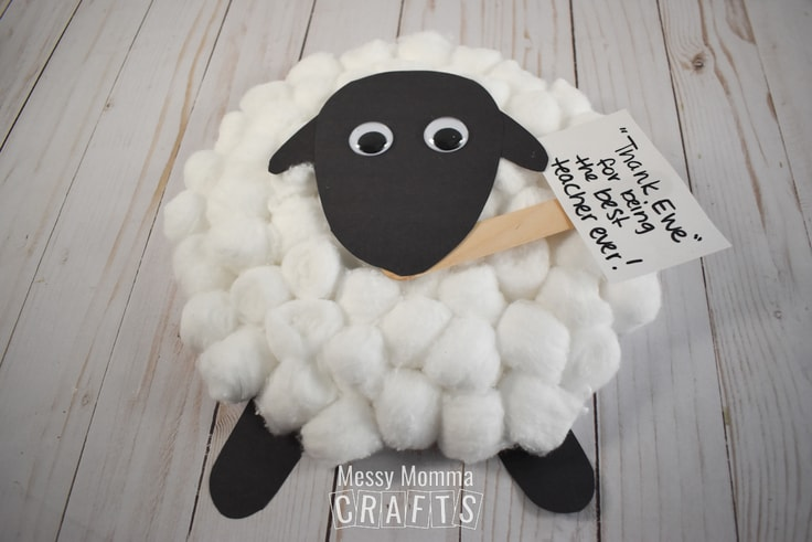 Cotton ball sheep craft holding a paper sign that reads