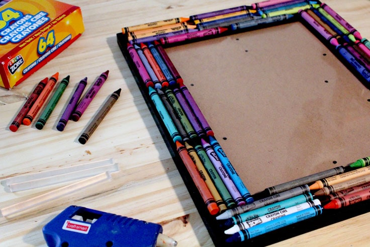 Crayons and a hot glue gun on a table beside a picture frame with crayons lined up around the border.