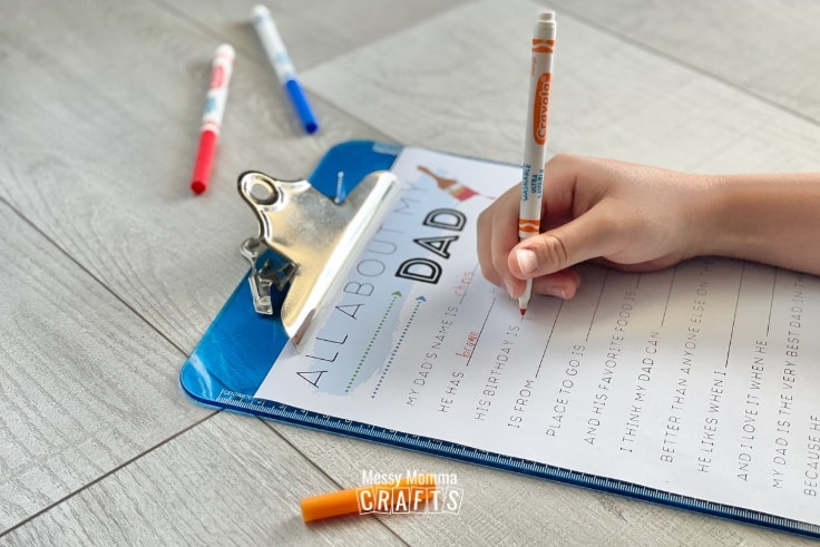 All About My Dad worksheet on a blue clipboard with a child's hand holding a marker.
