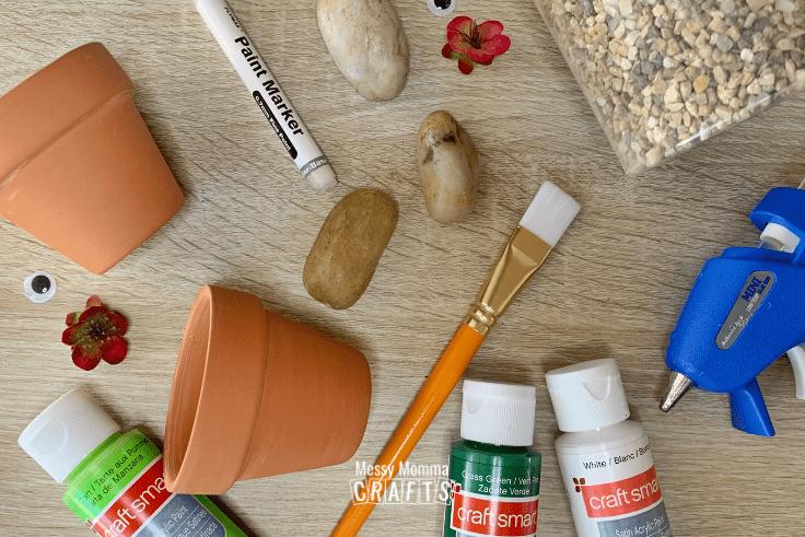 River rocks, gravel, terra cotta pots, a hot glue gun, and paint and a brush.