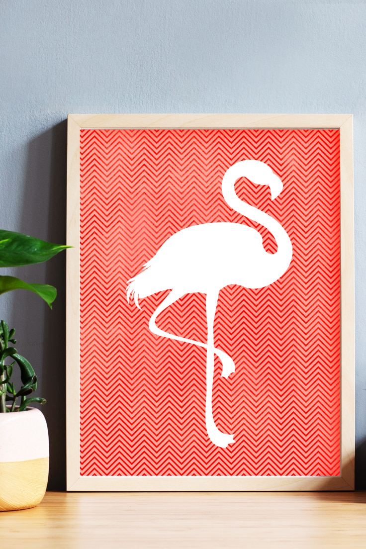 Preview of flamingo wall art in a wooden frame on desk with planter.