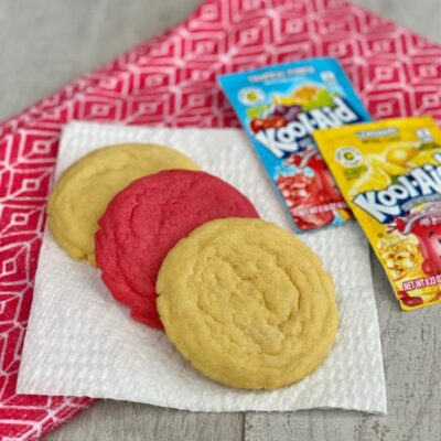Colorful Kool-Aid cookies with Kool-Aid mix on a wood background.