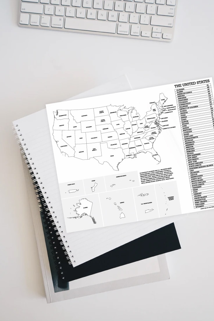 Preview of printable map of the united states on top of a stack of notebooks with computer keyboard.
