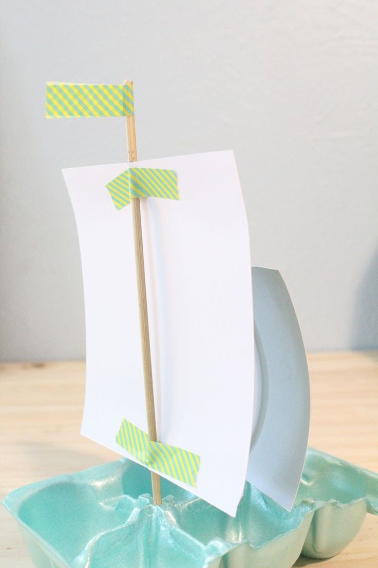 The back of a paper boat sail with washi tape attaching the ends to a wooden dowel.