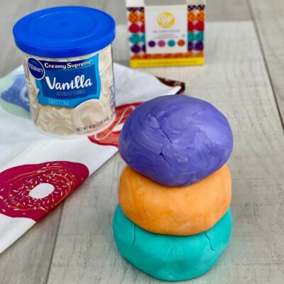 Stack of three balls of edible frosting play dough with a can of vanilla frosting & food coloring in the background.