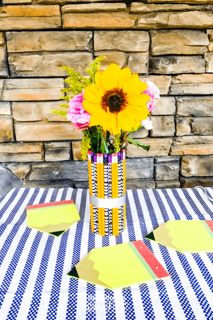 Vase made from pencils and filled with yellow and pink flowers on a table.