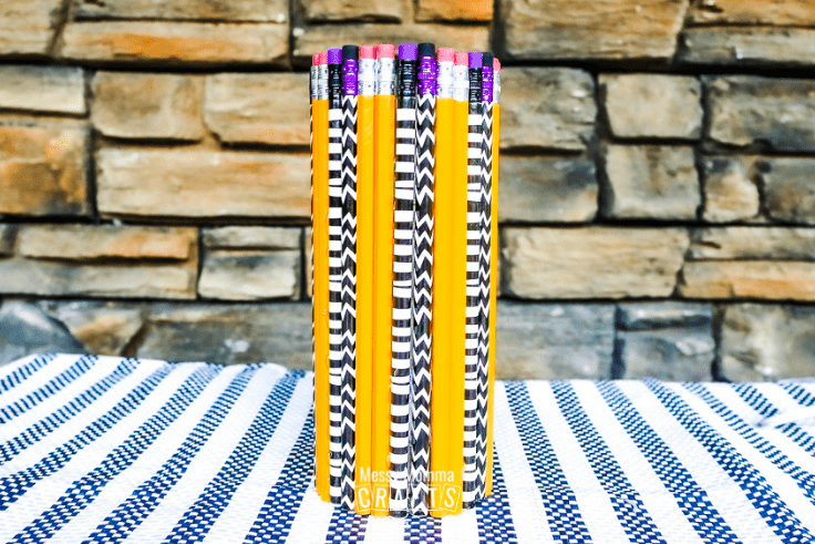 Yellow and striped pencils glued to a cylinder vase.