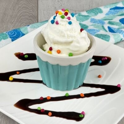 Blue bowl of ice cream topped with sprinkles on a white plate with chocolate syrup.