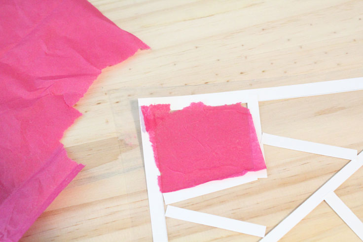 A piece of pink tissue paper with jagged edges stuck to a small section of the adhesive sheet.
