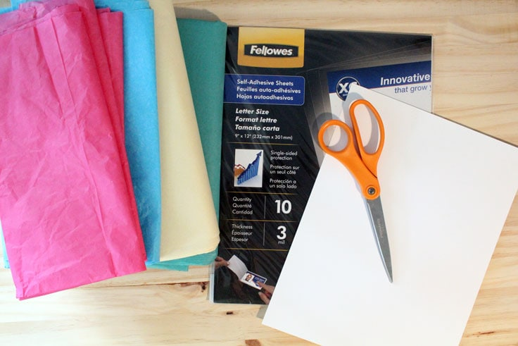 Pink, blue, yellow, and green tissue paper beside a package of self-adhesive sheets, card stock, and scissors.