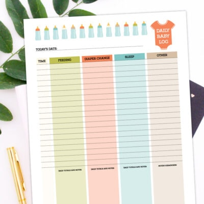 Preview of baby care log printable on desk with plant leaves and gold pen.