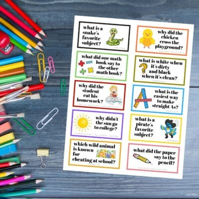 Free Printable Lunchbox Jokes for Kids on a wood backdrop with school supplies.
