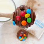 A spoon holding a hot cocoa bomb with M&Ms on the outside