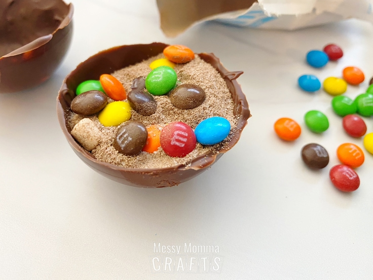 An open half of a hot cocoa bomb with cocoa powder and M&M minis inside of it