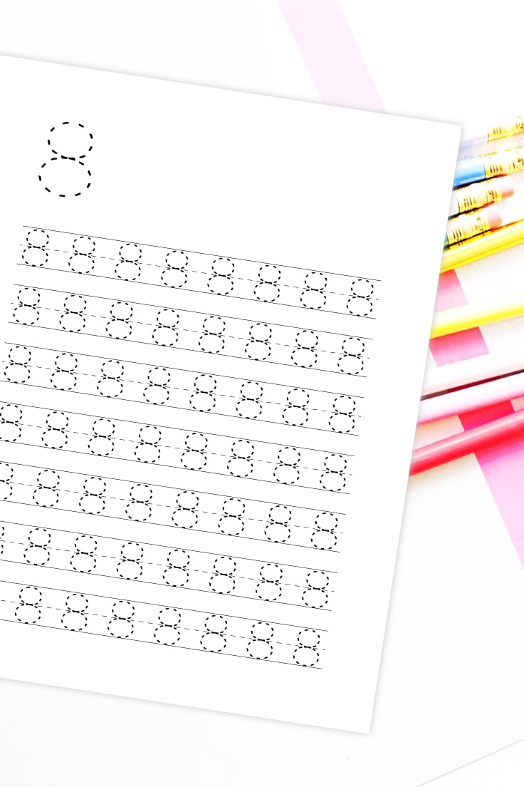 Flatlay view of white desk with variety of pencils with preview of number 8 printable number to trace worksheet.
