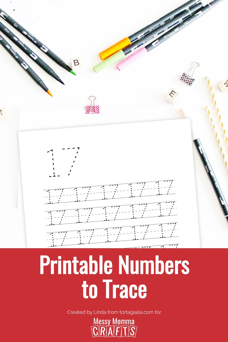 Flatlay view of white desk with colored markers, pencils, stationery clips and preview of number 17 printable number to trace worksheet.
