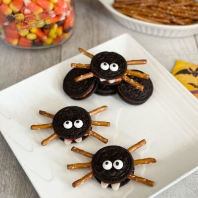 OREO Spider Cookies Spooky Halloween Treats on a white plate with Candy Corn in the background.